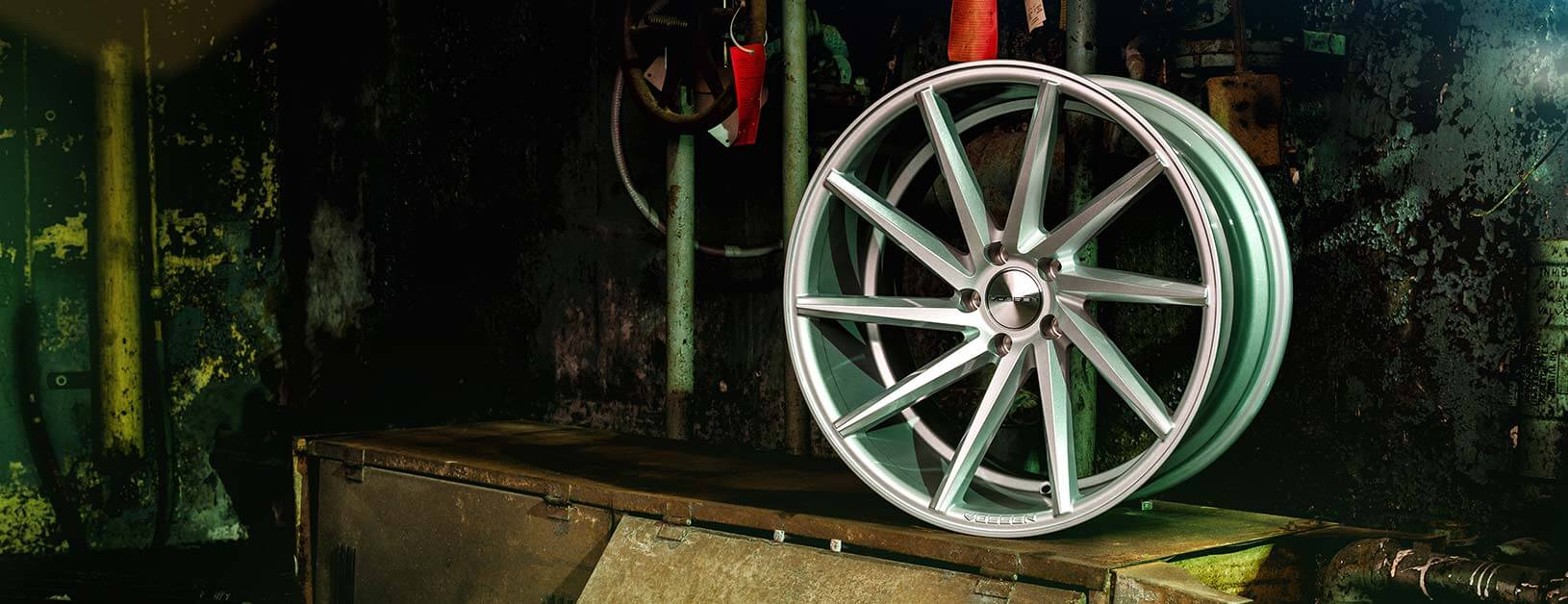 A Vossen CVT wheel in silver finish in front of an underground industrial backdrop